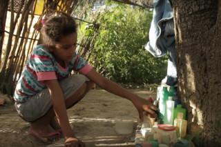 foto de uma menina abaixada, brincando com vários frascos em baixo de uma arvore.