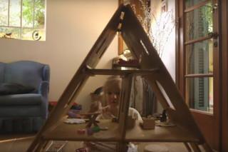 Uma menina brinca de casinha com uma casa de brinquedo feita de madeira, na casinha tem vários objetos em suas salas.