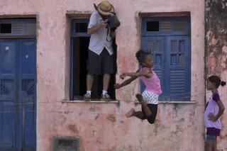 Foto composta por três pessoas, duas meninas negras brincando em frente de uma casa, enquanto uma salta a outra observa, e um homem de chapéu bege tira uma foto em cima de uma das duas janelas.