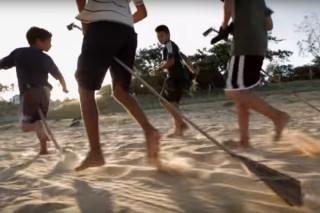 Quatro garotos correm em um chão de areia, em cima de cabos de gralho de uma arvore brincão de montar em cavalo.