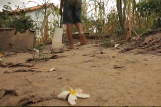 Foto de um garoto andando em um chão de terra, ele está de costas caminhando para longe da foto, uma casca de banana está jogada ao chão, o garoto puxa um carrinho de mão com sua mão esquerda, somente é possível ver a cintura para baixo do garoto.