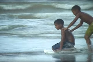 Foto de dois garotos negos, ambos estão sem camisa e brincando na beira do mar, em pé um garoto com bermudas verde, correndo empurra o outro garoto de bermuda azul, o garoto de bermuda azul está ajoelhado em uma prancha.