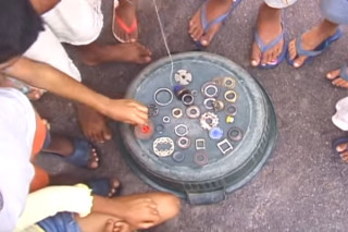 Foto composta por várias crianças em volta de uma bacia virada ao contrário, em cima da bacia tem várias engrenagens e peças.