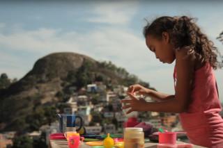 Foto de uma garota brincado de chá com uma mesa posta com várias peças de plástico, a garota serve o chá.