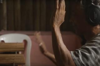 Foto de um home com fones de ouvido escuta musica com as mão levantadas.