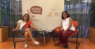 Foto composta por duas mulheres sentadas e sorrindo, a mulher da esquerda cruza as pernas.