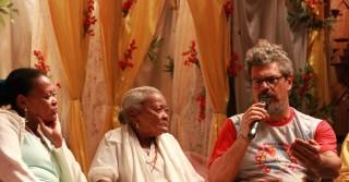 Foto ilustrando um diálogo entre três pessoas, a esquerda uma mulher negra acompanhada de uma senhora e um homem segurando um microfone.
