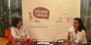 Foto composta por duas mulheres sentadas, a mulher da direita gesticula enquanto fala, a sua esquerda a outra mulher observa falar.